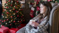 young beautiful woman is drinking tea near the Christmas tree video