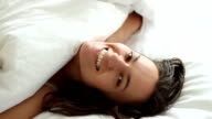 Young beautiful woman looks out under covers in bed video