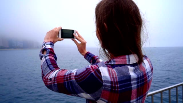 Young beautiful woman making mobile photo of modern city in fog video