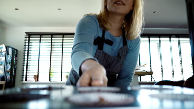 Young beautiful woman opens the oven and puts in baking tray. Attractive female cooking cupcakes in the kitchen video