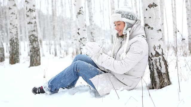 Young beautiful woman sculpts snowballs, sitting leaning against birch tree video