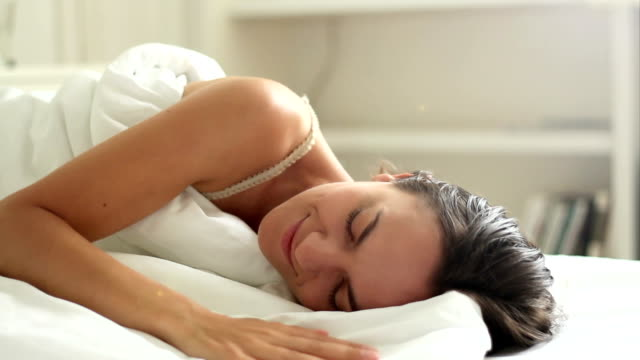 Young beautiful woman sleeping on bed in bedroom video