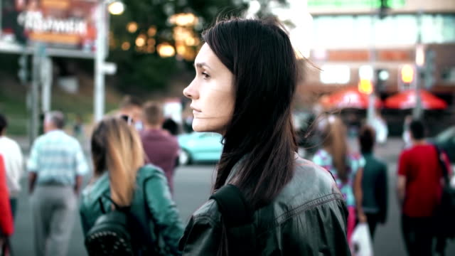 Young beautiful woman standing on the street. Brunette turns and looking to the camera. Slow motion video