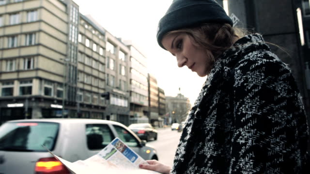 Young beautiful woman travelling with a map in the city streets. video