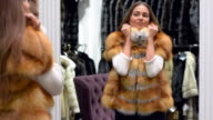 Young beautiful woman tries on clothes at the mall. video