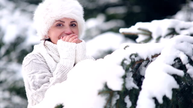 Young beautiful woman warms her hands in the snowy forest in winter wearing a fur hat video