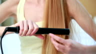 Young beautiful woman with long red hair uses a Curling iron for straightening hair, sitting on the bed in the bedroom. video