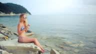 young beautiful woman with tropical fresh juice. girl in bikini at the sea video
