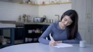 Young beautiful woman working from home signing documents video