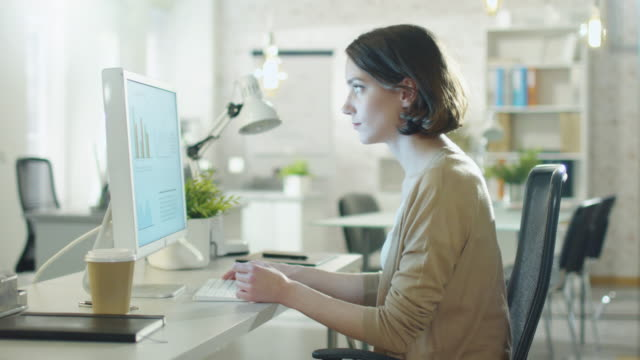 Young Beautiful Woman Works Sitting at Her Desk Using Personal Computer. She Works in a Modern Lightsome Office Space. video