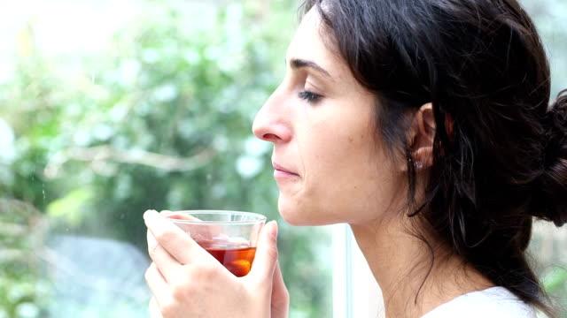 Young beautyfull woman drinking black tea video