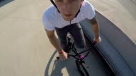 PORTRAIT: Young biker man riding bmx bike and jumping tricks in sunny park video