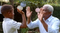 Young black boy playing clapping game with grandad in garden video