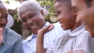 Young black boy playing with dad, uncle and grandad outdoors video
