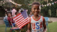 Young black boy waving US flag at 4th July family barbecue video