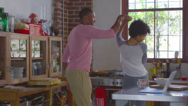 Young black couple dancing in kitchen, shot on R3D video