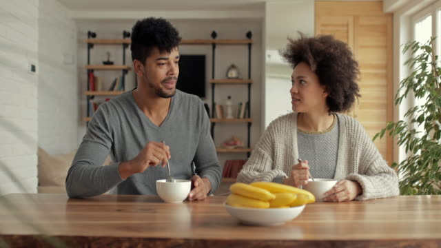Young black couple eating at dining table and communicating. video