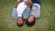 Young black couple lying on grass together, shot from above video