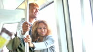 Young black couple riding train, looking out window video