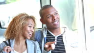 Young black couple riding train, talking, looking at view video