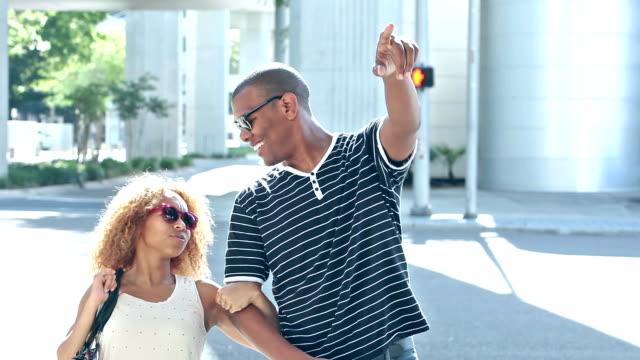 Young black couple walk across city street video