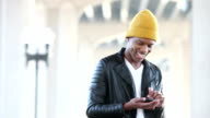 Young black man wearing beanie looking at mobile phone video