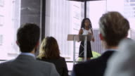 Young black woman presenting seminar to a business audience, shot on R3D video
