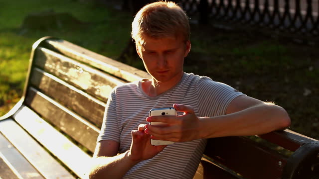 Young blond adult man writing sms message in park bench video