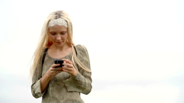 Young blond woman in nature outdoor text with mobile smartphone - slow-motion HD video footage video