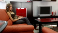 Young blond woman listens to the music in high-tech livingroom video