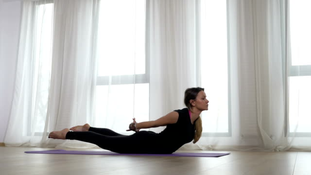 Young blonde adult woman doing bow pose during yoga workout video