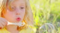 Young blonde girl blowing bubbles outside video