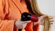 Young blonde girl in bathrobe blow drying her wet long hair with hairdryer video
