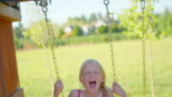 Young blonde girl swinging outside video