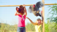 Young blonde girls throw chickens into the air video