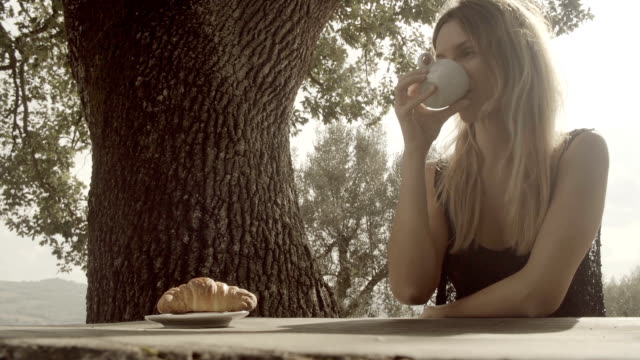 Young blonde happy woman has italian breakfast drinking coffee outdoor in nature rural scenic during summer sunny day morning in tuscany - slow-motion HD video footage video