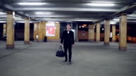 Young blonde man in a black suit with bow-tie walking on the parking with big leather bag. Slowmotion video