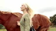 Young blonde smiling woman in nature outdoor stroke and hug brown horse and walk away - gimbal steadicam HD video footage video