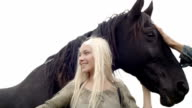 Young blonde smiling woman in nature outdoor strokes and hugs black horse - slow-motion HD video footage video
