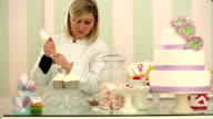 Young blonde woman confectioner garnishing in bakery video HD video