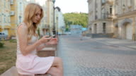 Young blonde woman use her phone outdoor video
