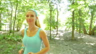 Young blonde woman using headphones during run on dirt path video