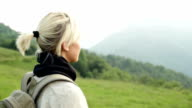 Young blonde woman walk on mountain with backpack video HD video