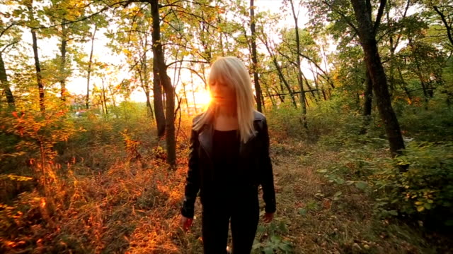 young blonde woman walking through the forest at sunset video