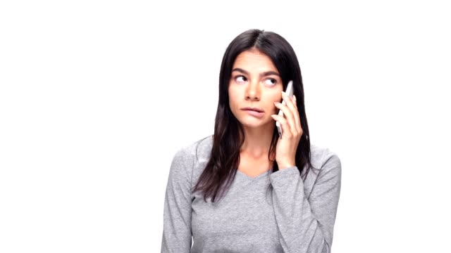 Young bored caucasian woman talking by phone over white background. video