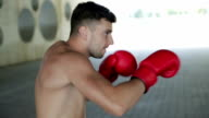 Young boxer in red gloves is training punching outdoors. video