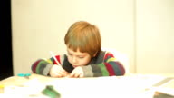 young boy absorbed scribbling video