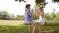 SLO MO DS A young boy and a girl blowing bubbles on a swing video