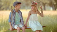 SLO MO Boy and girl holding hands on swing video
