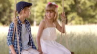 SLO MO Boy and girl on swing joining hands video